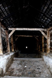 A very old stone staircase with a wooden roof. It leads up to the Church on the Hill and the cemetery. The exit is a small dot you can see in the middle of the photo